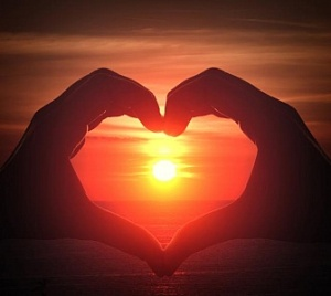 hand-silhouette-in-heart-shape-with-sunset-in-the-middle-and-oce