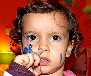 child-with-painted-face-scratching-her-nose-